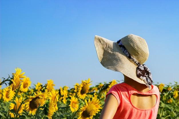 Mooi meisje in een hoed onder een zonnebloem