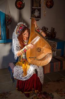 Mooi meisje in een hut in nationaal slavisch kostuum.