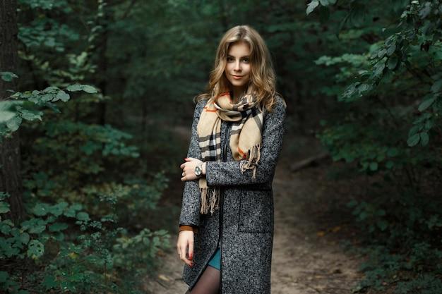 Mooi meisje in een jas en sjaal in een donker bos