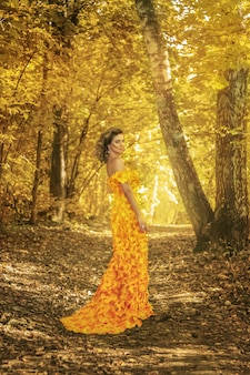 Mooi meisje in een jurk gemaakt van herfstbladeren in het park in de herfst seizoen. kunst foto.