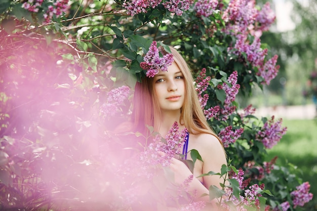 Mooi meisje in een jurk poseren in de buurt van een struik van seringen op een zomerse dag, paarse bloemen. lente portret van een kind in het park. grappige emoties op zijn gezicht.