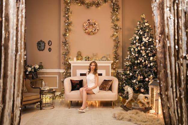 Mooi meisje in een jurk zit op een bank bij een boom en open haard in een luxe kerstinterieur