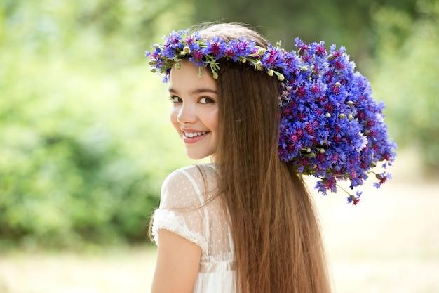 Mooi meisje in een krans van de korenbloemen en met een boeket in de mand.