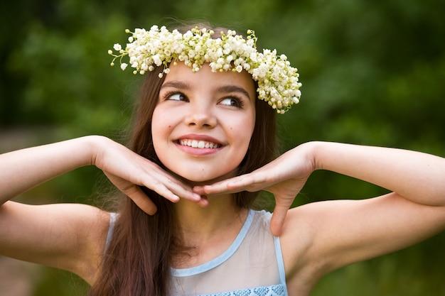 Mooi meisje in een krans van lelietje-van-dalen en met een boeket. vrouw verzamelt lelietje-van-dalen in de tuin.