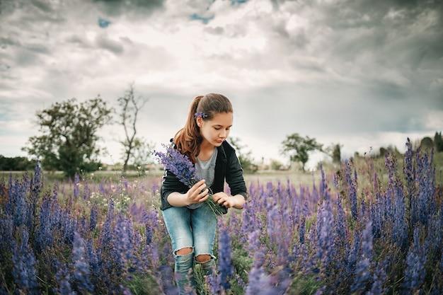 Mooi meisje in een lente veld verzamelt paarse bloemen.