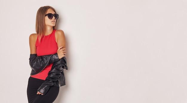 Mooi meisje in een leren jas en een rood t-shirt.