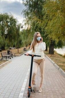 Mooi meisje in een masker rijden in het park op een elektrische scooter op een warme herfstdag