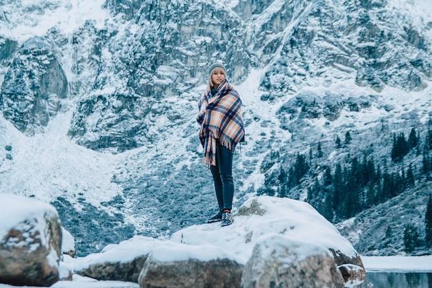 Mooi meisje in een poncho op een achtergrond van besneeuwde bergen