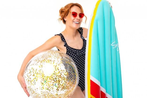 Mooi meisje in een retro badpak houdt een surfplank en bal met sparkles op een witte muur