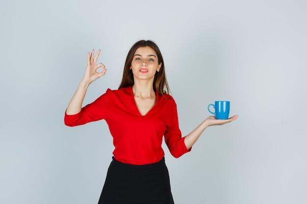 Mooi meisje in een rode blouse, een zwarte rok die een beker vasthoudt, een goed gebaar toont en er tevreden uitziet, vooraanzicht.