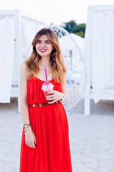 Mooi meisje in een rode jurk die zich op een strand bevindt en wijd lacht