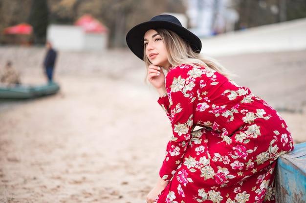 Mooi meisje in een rode jurk en zwarte jas zit op een blauwe boot