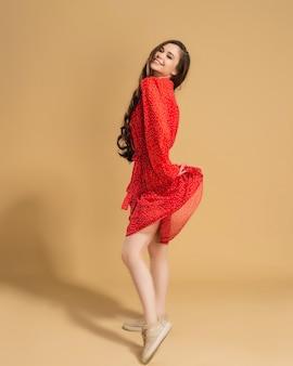 Mooi meisje in een rode jurk met polka dots tilt de rand van de jurk op op een pastel oranje.