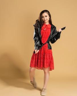 Mooi meisje in een rode jurk met stippen en een zwart leren jasje bindt een riem op een pastel oranje.