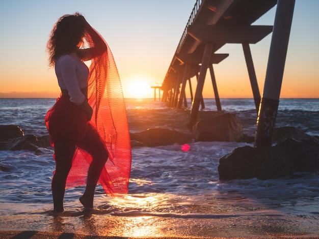 Mooi meisje in een rode jurk op het strand bij zonsopgang