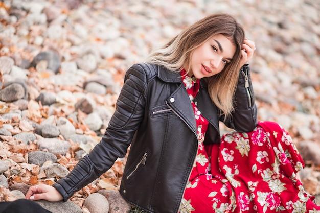 Mooi meisje in een rode jurk zittend op de rotsachtige kust