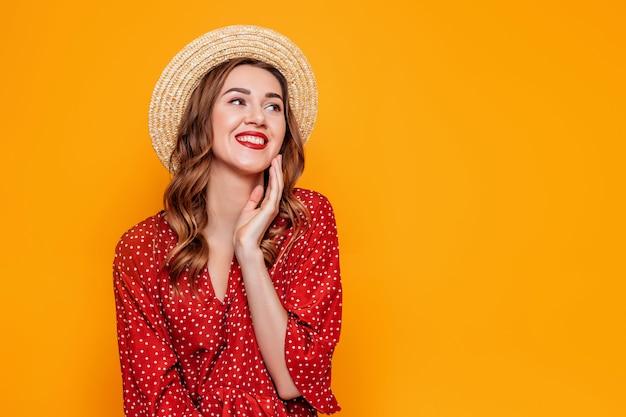 Mooi meisje in een rode kleding glimlacht dat over oranje achtergrond wordt geïsoleerd