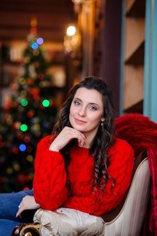 Mooi meisje in een rode trui in de buurt van de kerstboom.
