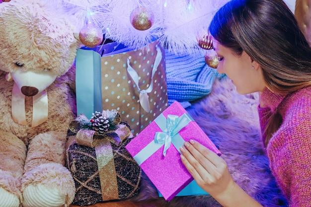 Mooi meisje in een roze jurk in de buurt van de versierde kerstboom opent een nieuwjaarsgeschenk