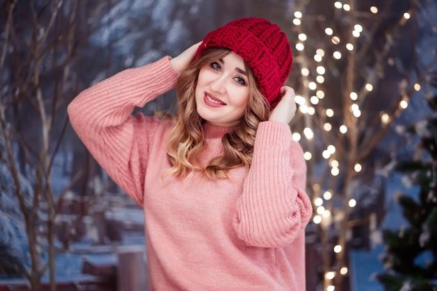Mooi meisje in een roze trui en een rode hoed