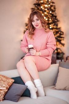 Mooi meisje in een roze trui met een kopje koffie en marshmallows