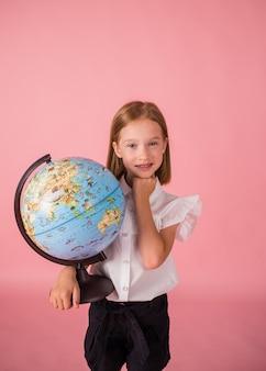 Mooi meisje in een schooluniform houdt een wereldbol op een roze achtergrond met een plek voor tekst