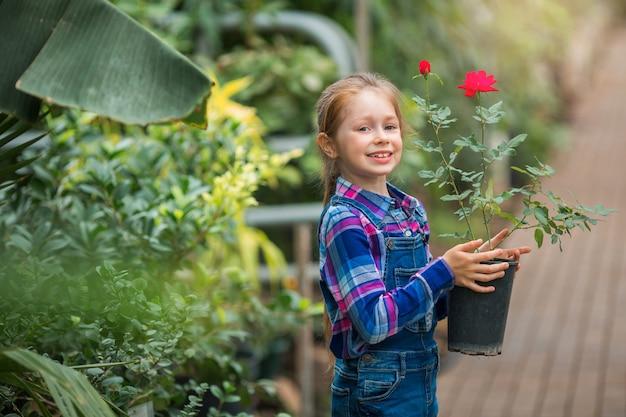 Mooi meisje in een serre tuin met een bloeiende plant in een pot in haar handen