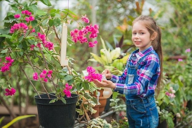 Mooi meisje in een serre tuin zorg voor bloeiende planten