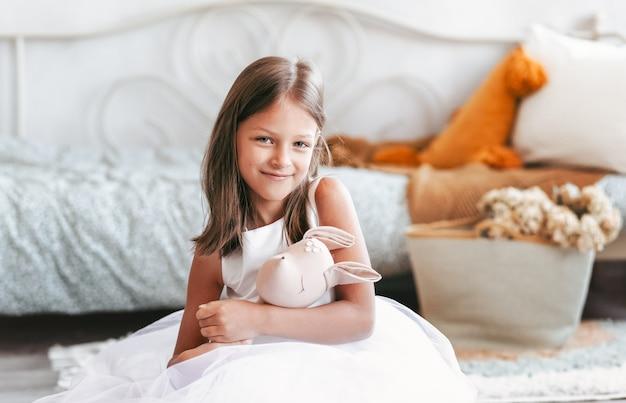 Mooi meisje in een slimme jurk speelt met een stuk speelgoed op de vloer in de kinderkamer