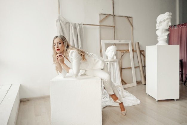 Mooi meisje in een stijlvolle witte pak zit op een witte kubus in een galerij