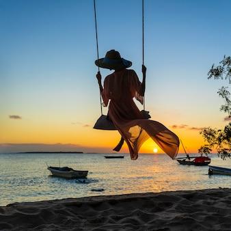 Mooi meisje in een strohoed en een pareo die op een schommeling op het strand slingeren tijdens zonsondergang van het eiland van zanzibar, tanzania, afrika. reis- en vakantie concept