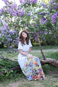 Mooi meisje in een strohoed en in een lange jurk in een tuin lila zomerpicknick die in het weekend rust