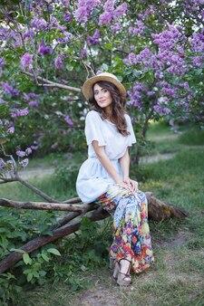 Mooi meisje in een strohoed in vintage jurk in lila tuin zomerpicknick en rusten in het weekend