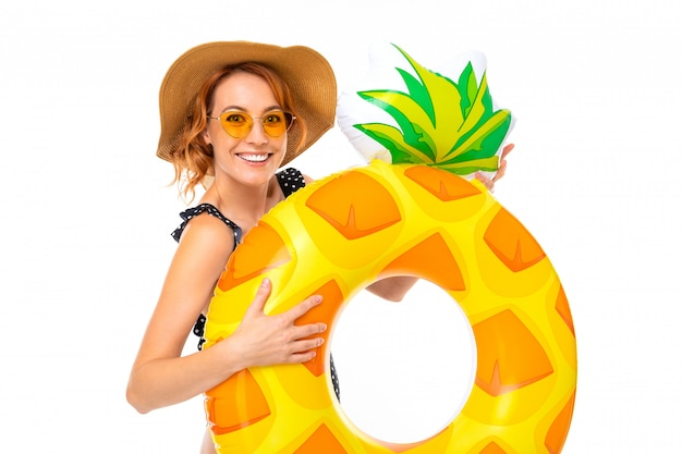 Mooi meisje in een strohoed met een ananasvormige zwemmende cirkel op wit