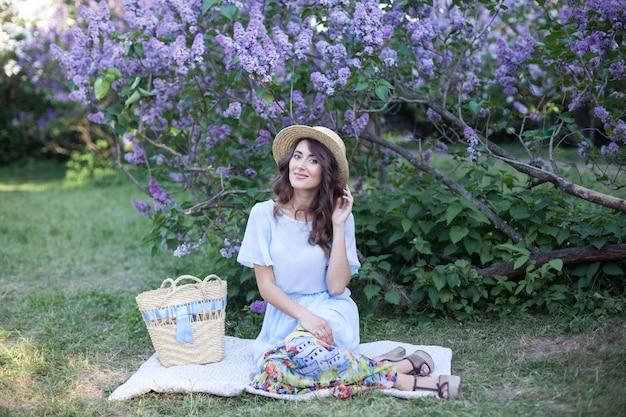 Mooi meisje in een strohoed zittend in de buurt van een bloeiende lila in de stralen van de ondergaande zon zomerpicknick