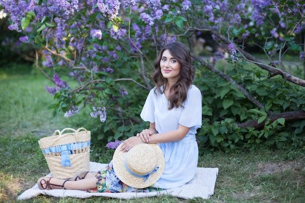 Mooi meisje in een strohoed zittend in de buurt van een bloeiende lila zomerpicknick vintage mode