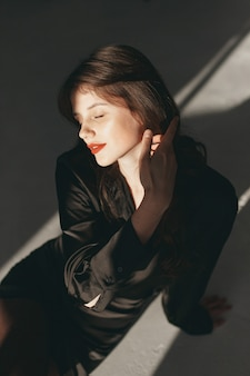 Mooi meisje in een studio. stijlvolle vrouw in een zwarte jurk.