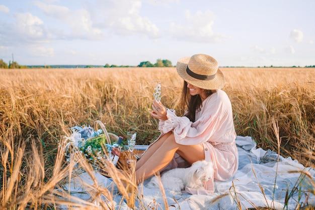 Mooi meisje in een tarweveld met rijpe tarwe in handen
