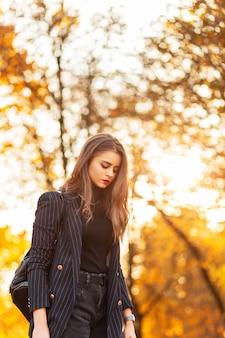 Mooi meisje in een trendy pak met een stijlvolle blazer en een trui met een mode-rugzak loopt in het park met gouden herfstgebladerte bij zonsondergang