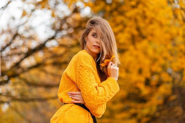 Mooi meisje in een trendy vintage gebreide gele trui in een herfstpark met gekleurd geel herfstblad