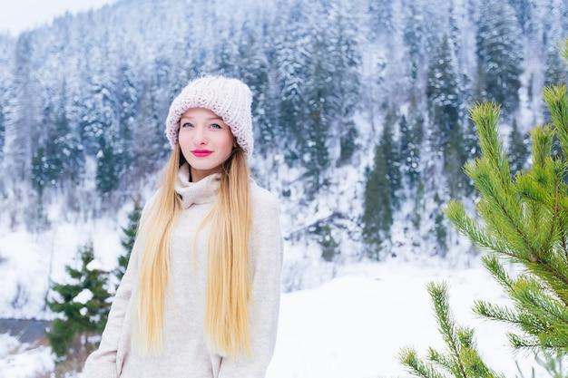 Mooi meisje in een trui en pet op haar hoofd