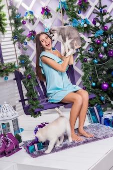 Mooi meisje in een turquoise jurk zittend op een schommel en kerstversiering