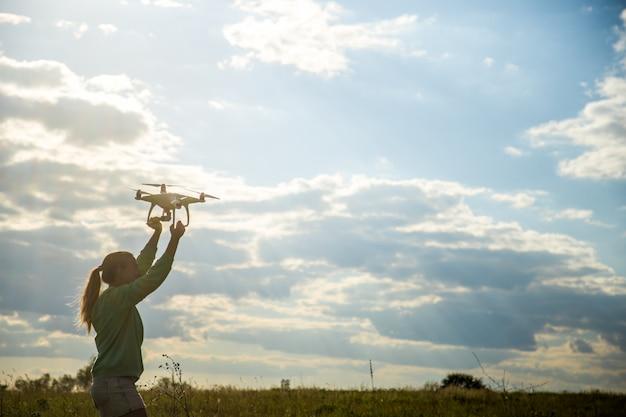 Mooi meisje in een veld lanceert de drone in de lucht