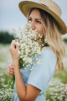 Mooi meisje in een veld van madeliefjes. meisje in een strooien hoed en een blauwe jurk. kamille veld in de zomer