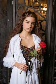 Mooi meisje in een vintage stijl jurk met een rode roos in haar handen