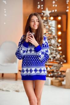 Mooi meisje in een warme vakantiesweater met een kop warme thee met kaneel