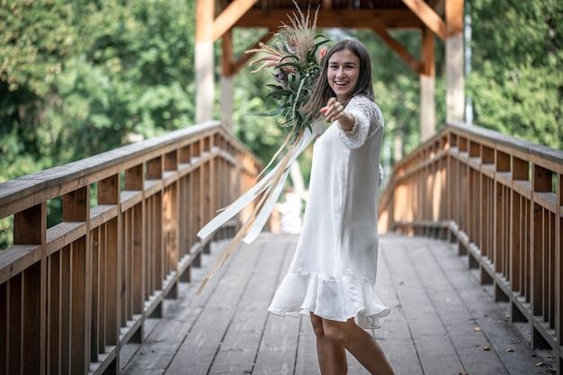 Mooi meisje in een witte jurk met een boeket exotische bloemen op een houten brug.