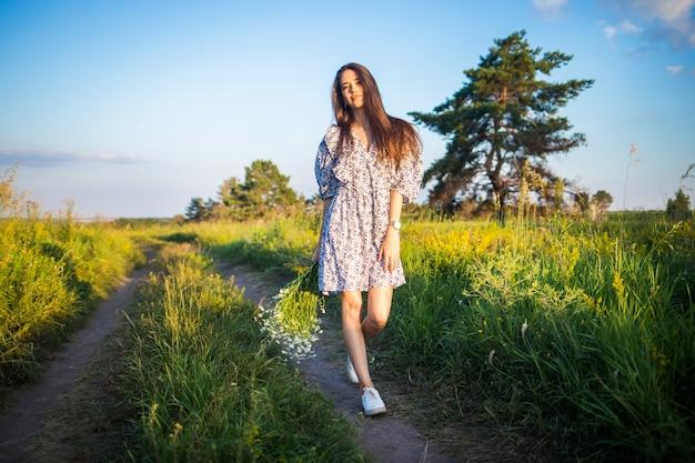 Mooi meisje in een witte jurk met een boeket loopt langs de weg in de velden