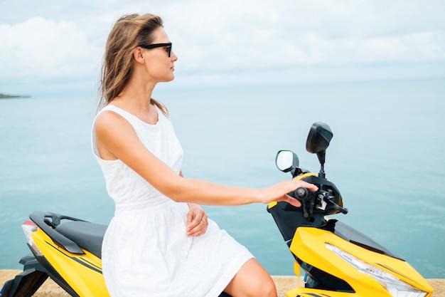 Mooi meisje in een witte jurk op een scooter