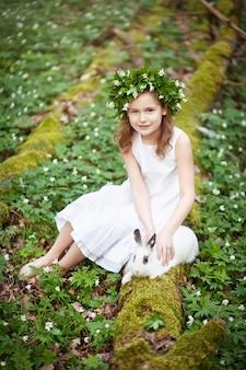 Mooi meisje in een witte jurk plaing met wit konijn in het voorjaar hout.